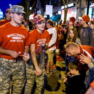 Members of UW-Madison's Army-ROTC hand out candy as thousands of spectators and children line State Street.