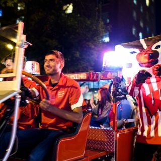 UW-Madison's mascot Bucky Badger cheers as engineering student Saager Paliwal drives the Bucky Wagon travels down State Street.