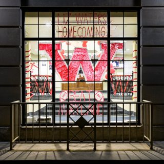 Hand-painted in red, the letter W and a homecoming message displayed on the main entrance window at Elizabeth Waters Residence Hall.