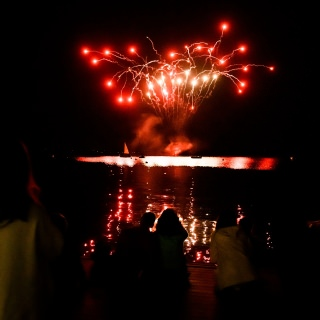 UW-Madison alumni, students and members of the Madison community line Goodspeed Family Pier to take in a firework display over Lake Mendota.