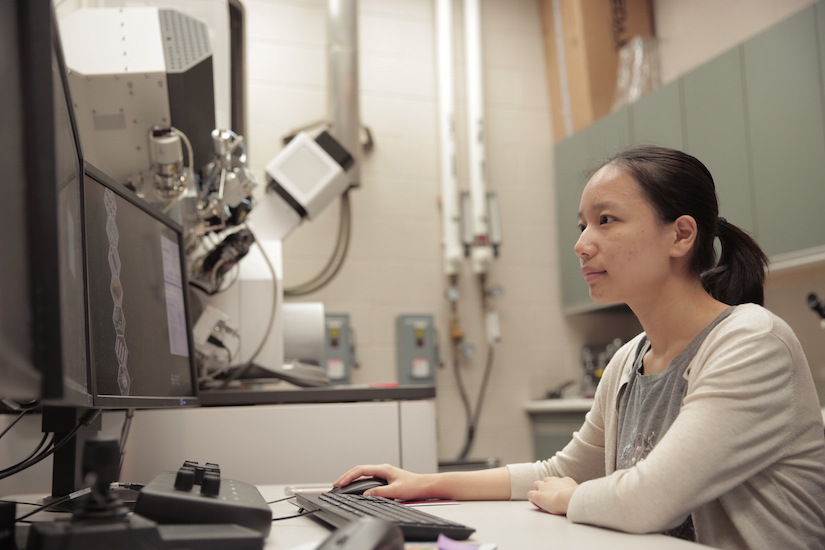 Photo: Yingxin Guan sitting in front of microscope