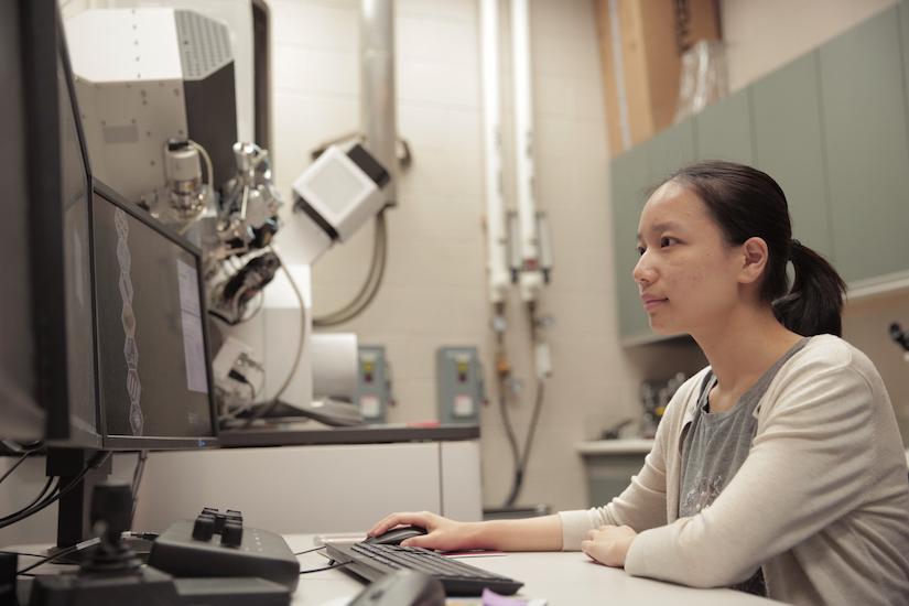 Photo: Yingxin Guan sitting in front of microscope