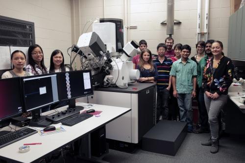Photo: Students standing around microscope