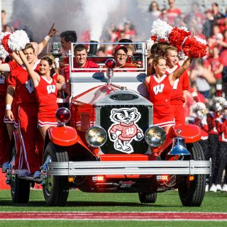 Members of UW Spirit Squad ride the Bucky Wagon onto the field at Camp Randall Stadium before the homecoming football game. The driver of Bucky Wagon is Glenn Bower, the manager of the wagon and automotive faculty adviser for UW-Madison's College of Engineering