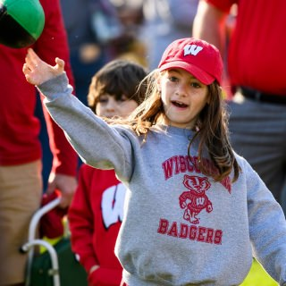 Badger fan Aubrey Hyland, 9, tosses a football during Badgerville Pre-Game Tailgate Party at Engineering Mall prior to the Wisconsin Badgers homecoming football game.