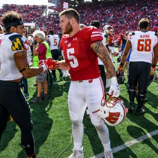 Following a hard-fought game, Maryland player Ty Johnson (#6) and Wisconsin running back  Garret Dooley (#5) exchange handshakes on the field.