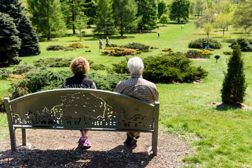 Photo: Couple sitting on bench looking at Longnecker Gardens
