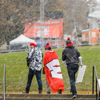 A Wisconsin athletic flag doubles as protection against the weather.