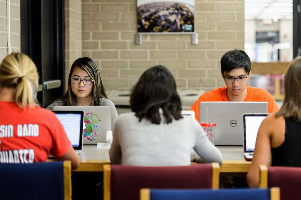 Photo: Students sitting at a table looking at laptop screens