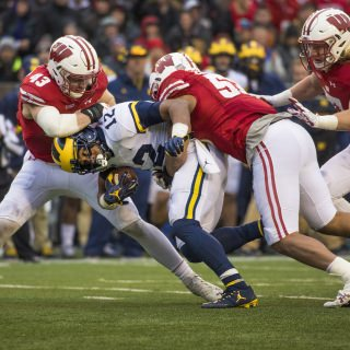 Linebacker Ryan Connelly, left, and T.J. Edwards bring down Michigan running back Chris Evans.