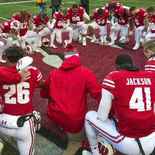 Team members kneel and pray together after their final home game of the season.
