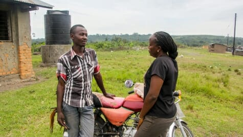 HAC program director Carolyne Ariokot and borrower Mike Nsubuga discuss logistics. Mike paid off the first motorcycle loan in February, 2017, and now owns this cycle.
