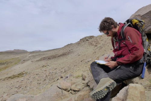 Photo: Nathan Andersen sitting at volcano site taking notes