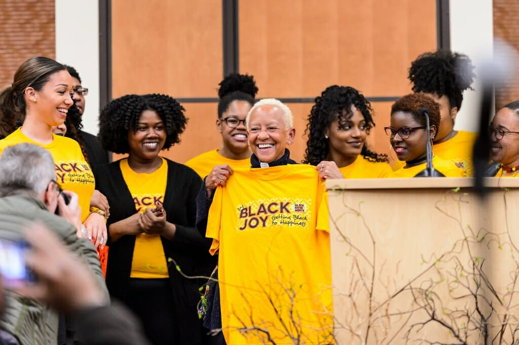 Photo: Nikki Giovanni being presented with T-shirt
