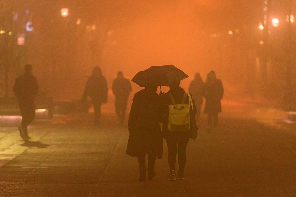 Photo: People under umbrella walking in fog