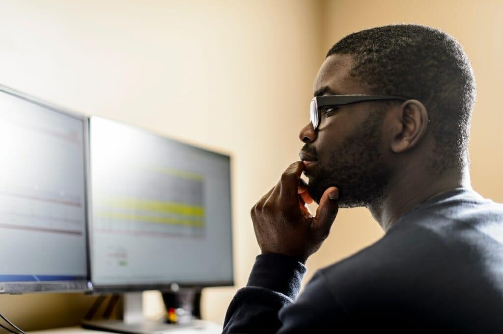 Photo: Kweku Brewoo looking at computer screens