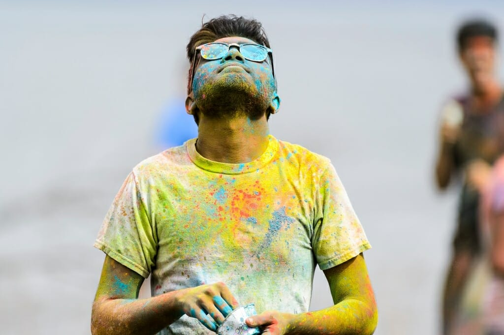 Photo: Man in sunglasses covered with multicolored powder