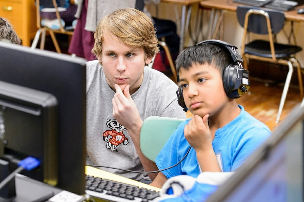 Photo: College student and elementary student looking at computer screen with similar poses of hands on their chins