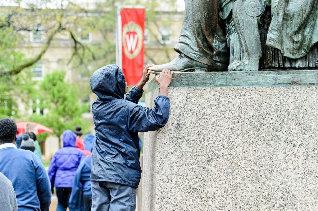 Photo: Young student touching foot of Lincoln statue