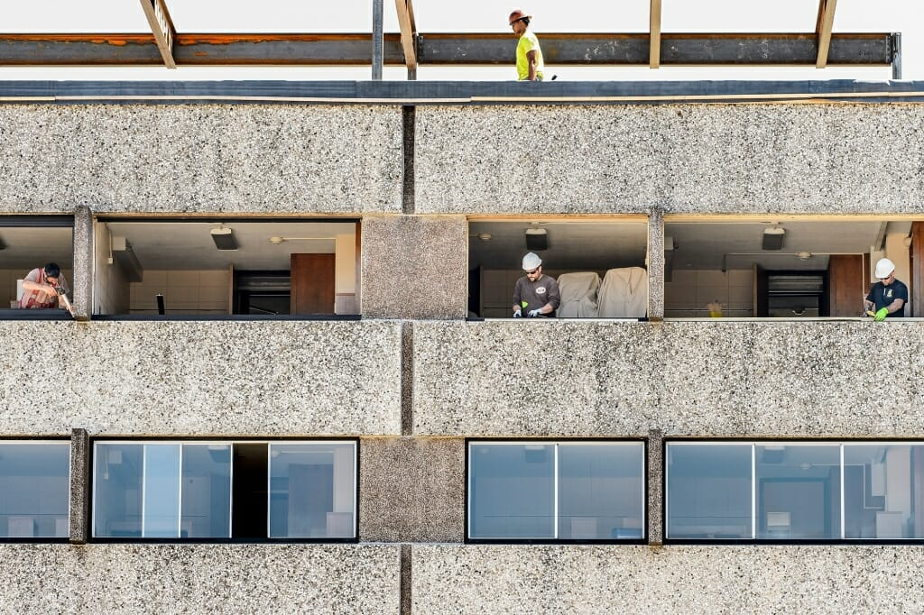 Photo: Workers standing in windows of Witte Residence Hall