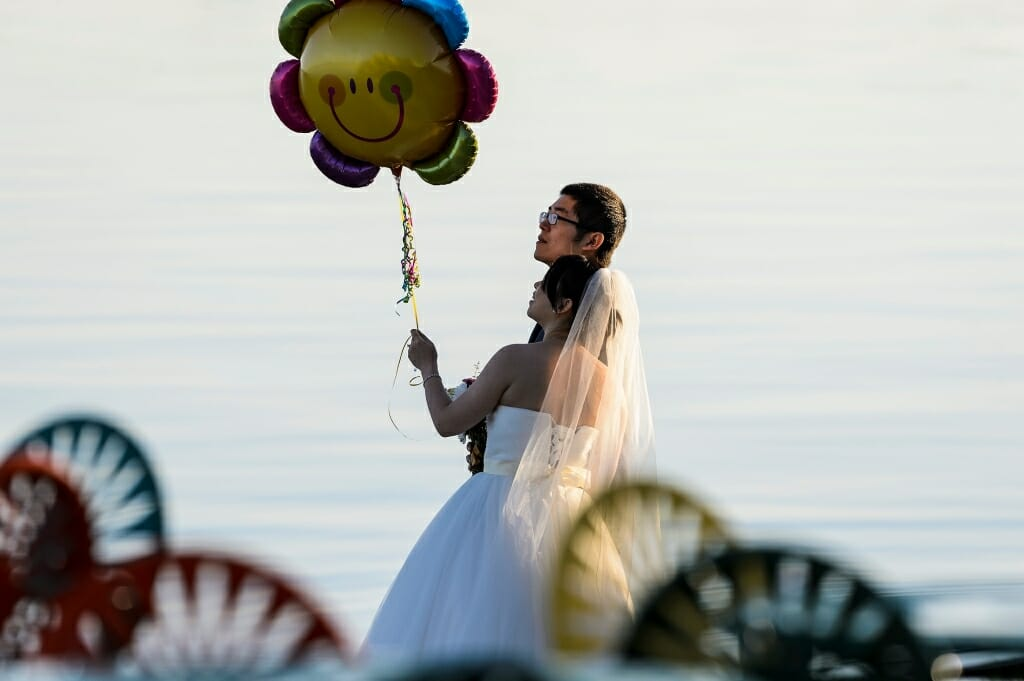 Photo: Couple in wedding clothes holding a smiley-face balloon by the lake