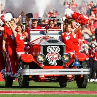 Members of spirit squad ride the Bucky Wagon onto the field at Camp Randall Stadium before the Homecoming football game against Maryland. The driver is Glenn Bower, the manager of the wagon and automotive faculty adviser for UW-Madison's College of Engineering.