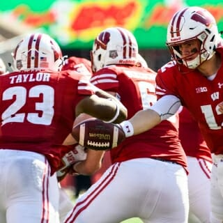 Wisconsin quarterback Alex Hornibrook (12) hands off the ball to running back Jonathon Taylor (23) against Maryland.