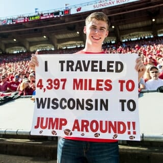 Martin Janku, a Badger and Jump Around fan from the Czech Republic holds up a sign describing his commitment during the Homecoming game.