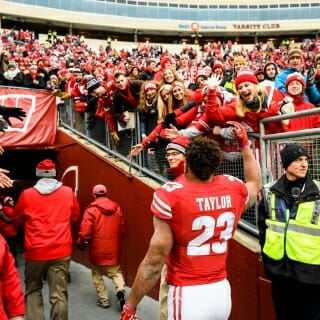 Badgers players, including running back Jonathan Taylor, wave to cheering fans after defeating Wisconsin.