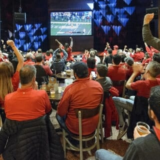 Badger fans gather inside The Sett at Union South to watch the Big Ten Championship game.