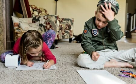 Photo of two siblings coloring.