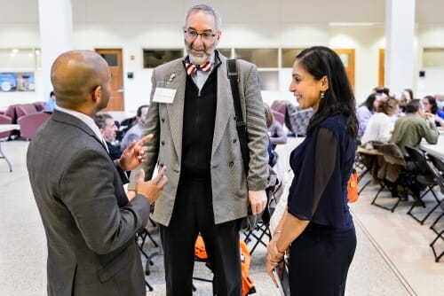 Photo of Washington University researcher David Gutmann, center, speaking with UW–Madison's Dhanu Shanmuganayagam, left, and Neha Patel.