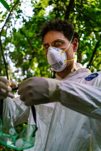 Photo: Tony Goldberg wearing face mask and protective gear in jungle