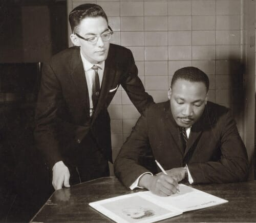 Photo: Jim Ehrman stands behind Martin Luther King, who is writing on a book or pamphlet