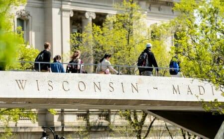 "Photo: Students walking across pedestrian bridge that says ""Wisconsin-Madison"""