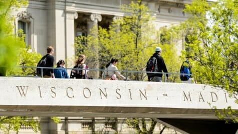 Photo: Students walking across pedestrian bridge that says