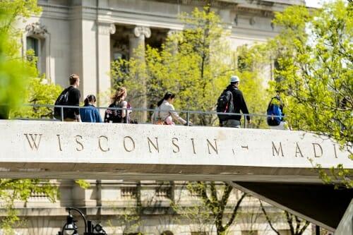 Photo: Students walking across pedestrian bridge that says
