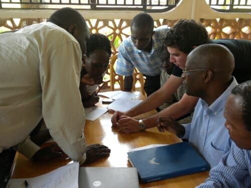 Photo: American trainer showing test to Uganda staff gathered around a table