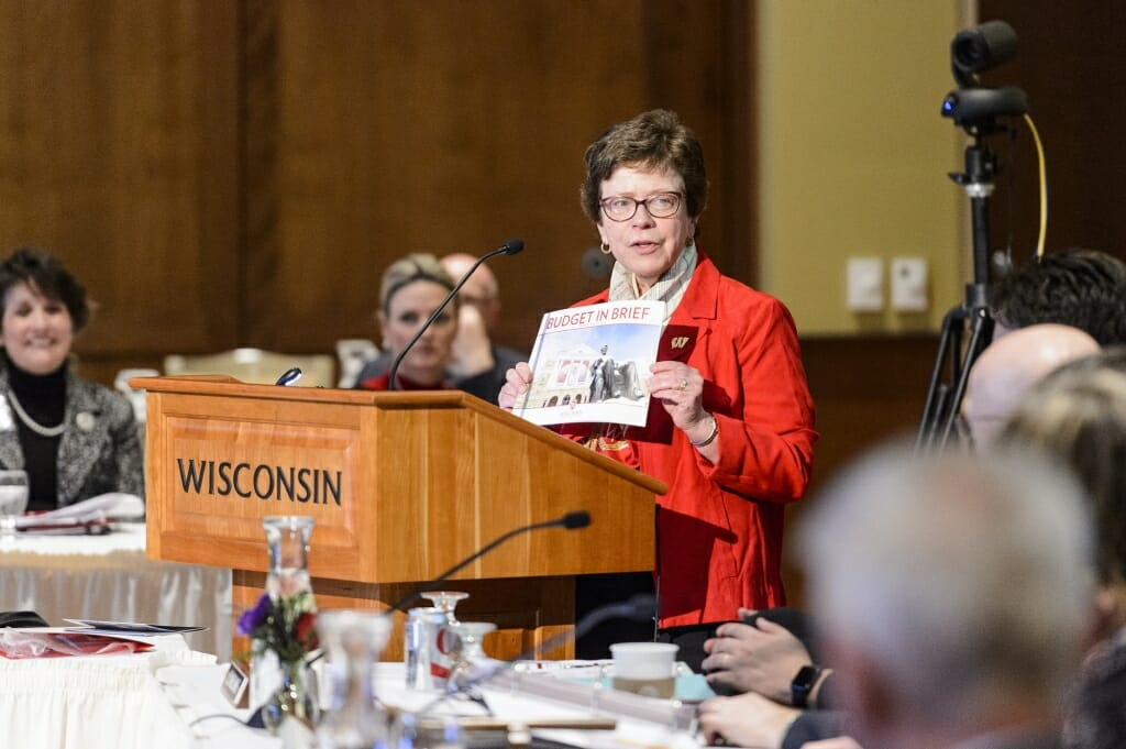 Photo: Rebecca Blank holding up budget booklet at podium