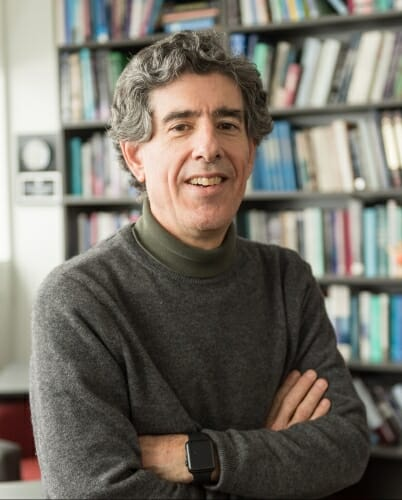 Photo: Richard Davidson, arms crossed, in front of bookshelf