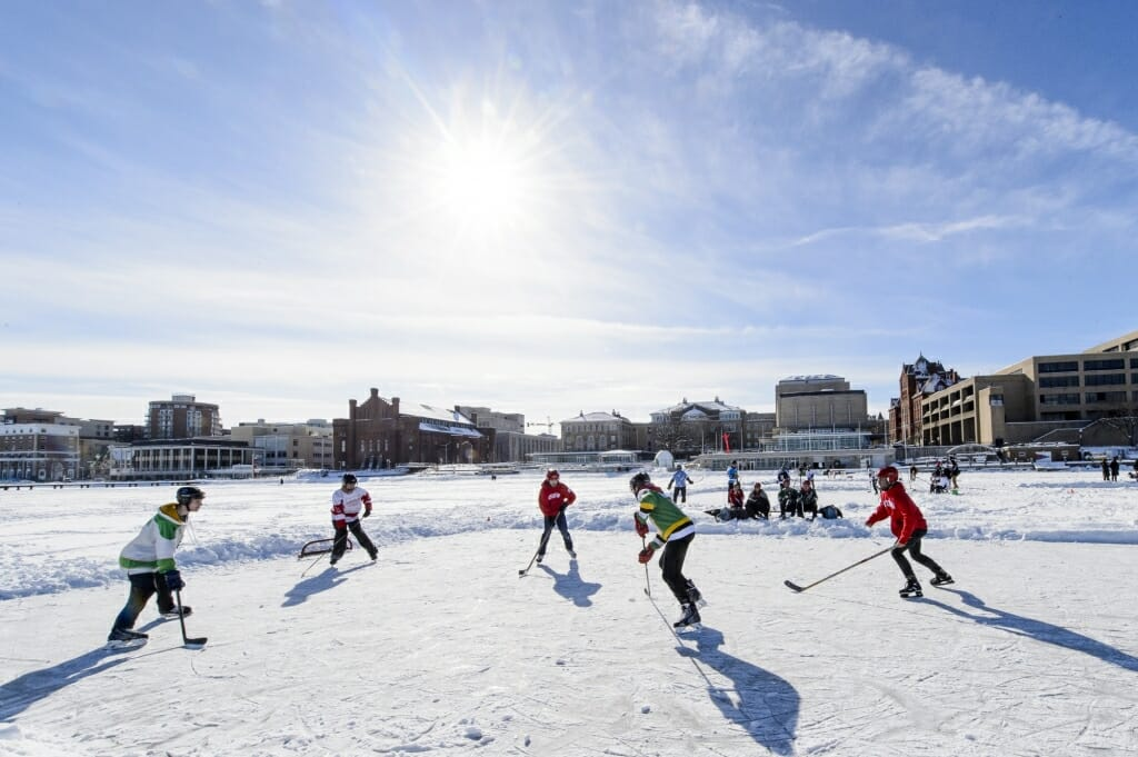 Photo of students facing off during the pond hockey tournament on Lake Mendota.