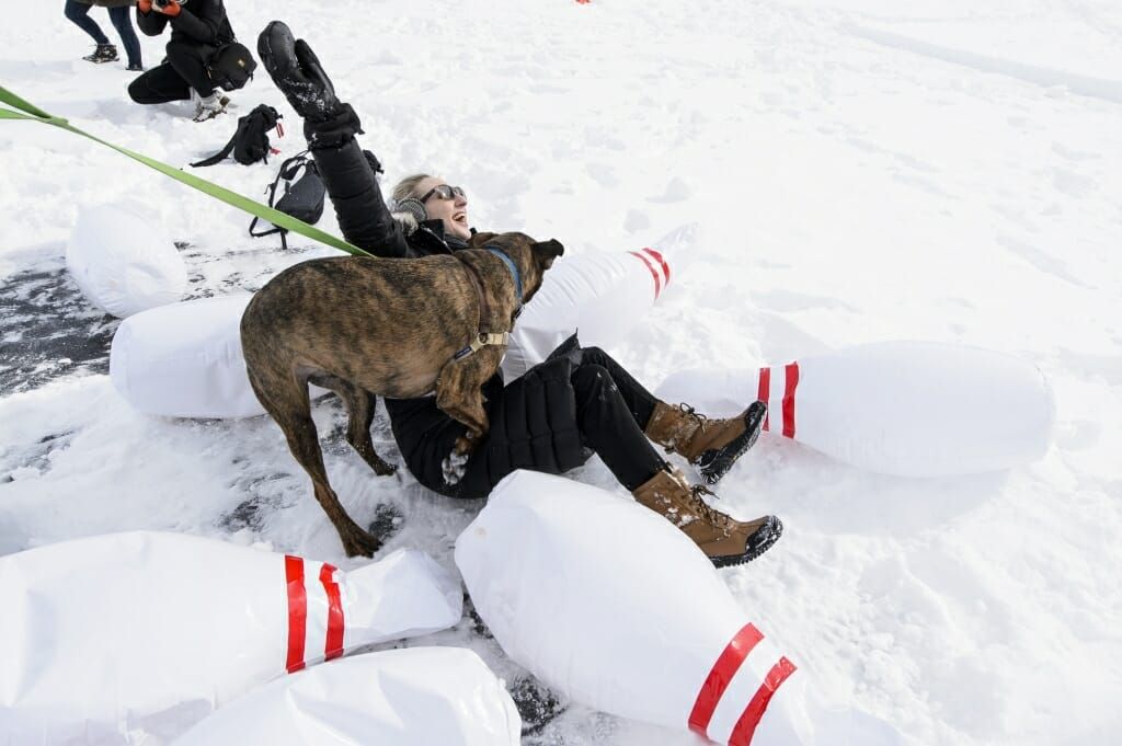 Photo of Carley Varo and her dog Moose tumbling amid the bowling pins.