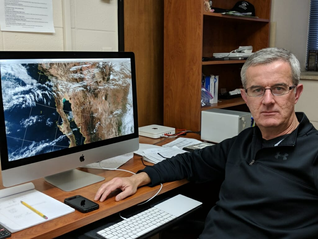 Photo: Liam Gumley sitting in front of computer screen displaying satellite image