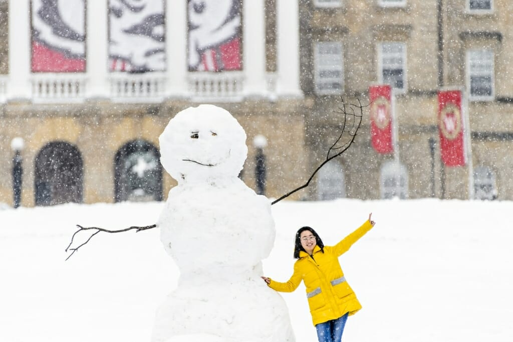 A student takes a photo with a snowman near the base of Bascom Hill.
