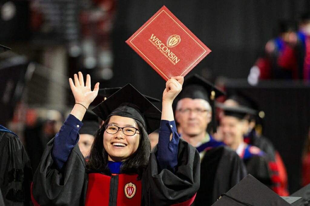 Photo: Doctoral graduate holding up hands with diploma cover