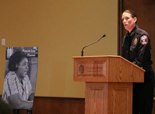 Photo: Kristen Roman speaking at podium with Fanny Lou Hamer poster next to her