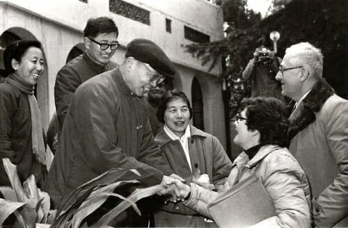 Photo: Nanjing University President Kuang Yaming shakes hands with Millie Shain, wife of UW-Madison Chancellor Irving Shain (right), during the 1979 visit of a UW delegation to China.