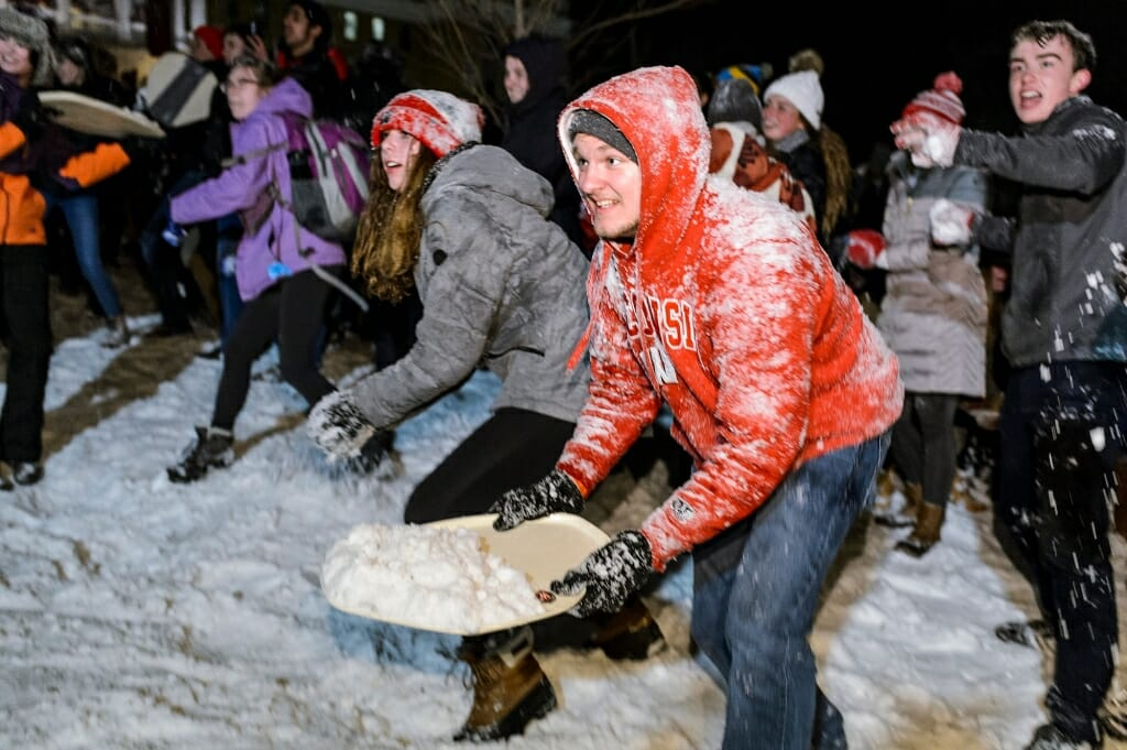 Photo of student scooping snow with a tray.