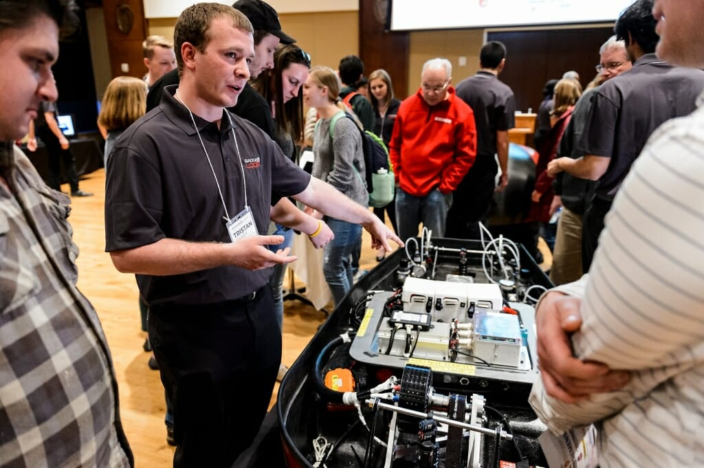 UW-Madison Badgerloop battery team lead Tristan Steiner, left, explains the pod to guests.