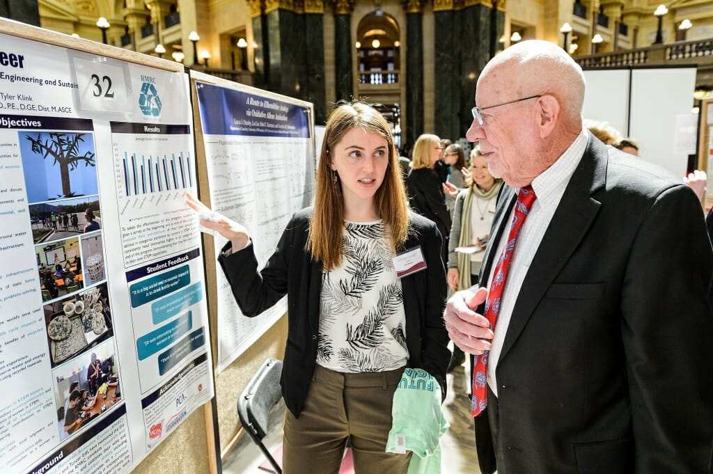 Sen. Fred Risser listens to UW-Madison student Morgan Sanger talk about her and her teammates' research project.